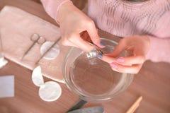 La donna taglia la cuticola con la pinza Fa il manicure lei stessa Mani del primo piano Strumenti del manicure sulla tavola Vista Fotografie Stock