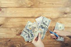 La donna taglia i soldi fotografia stock
