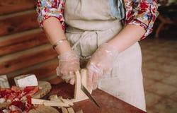 La donna taglia il bordo dei lobuli del formaggio a pasta dura della carne fotografie stock libere da diritti