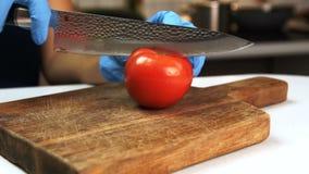 La donna taglia il pomodoro a metà con il coltello in cucina della casa stock footage