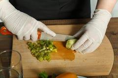 La donna taglia un coltello su un piatto di legno del kiwi in pezzi Fotografia Stock
