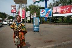 La donna tanzaniana dalla carnagione scura sta sulla via circondata da outd Immagine Stock