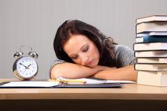 La donna a tarda notte di lavoro cade addormentato allo scrittorio Immagine Stock