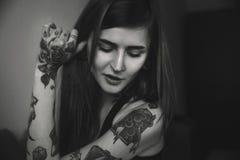 La donna tatuata giovani con capelli lunghi posa, guardando giù Fotografia Stock Libera da Diritti