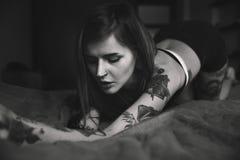 La donna tatuata giovani con capelli lunghi posa nel letto Fotografie Stock Libere da Diritti