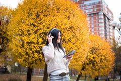 La donna teenager felice che ascolta la musica e si rilassa nel parco di autunno Alberi gialli, bello tempo di caduta Fotografia Stock