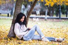 La donna teenager felice che ascolta la musica e si rilassa nel parco di autunno Alberi gialli, bello tempo di caduta Fotografia Stock Libera da Diritti