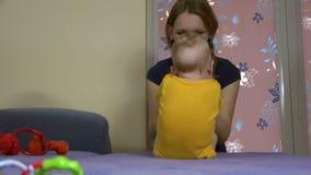 La donna tenera con il bambino sveglio fa gli esercizi di addominali sul sofà 4K video d archivio