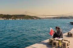 la donna tiene la bandiera del turco con la vista del bosphorus Immagini Stock Libere da Diritti