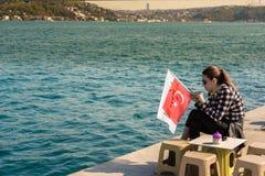 la donna tiene la bandiera del turco con la vista del bosphorus Fotografie Stock