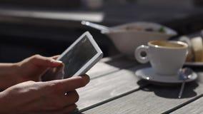 La donna tiene la compressa sulla tavola con la tazza di caffè stock footage