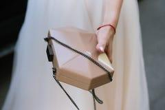 La donna tiene a disposizione una piccola borsa femminile immagini stock libere da diritti