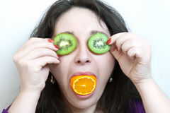 La donna tiene due fette di kiwi prima dei suoi occhi Fotografia Stock