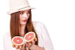 La donna tiene due halfs degli agrumi del pompelmo in mani Fotografie Stock