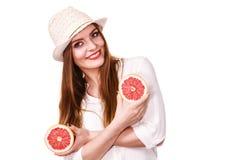La donna tiene due halfs degli agrumi del pompelmo in mani Immagine Stock