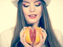 La donna tiene due halfs degli agrumi del pompelmo in mani Immagini Stock