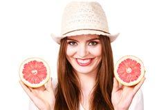 La donna tiene due halfs degli agrumi del pompelmo in mani Fotografie Stock Libere da Diritti