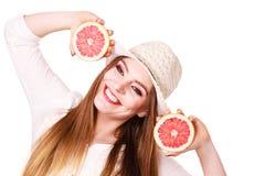 La donna tiene due halfs degli agrumi del pompelmo in mani immagine stock libera da diritti