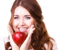 La donna tiene la frutta della mela vicino al fronte, isolato Immagini Stock