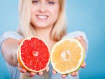 La donna tiene gli agrumi del pompelmo in mani Fotografie Stock