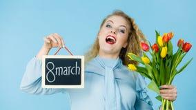 La donna tiene i tulipani, bordo con testo l'8 marzo Immagini Stock