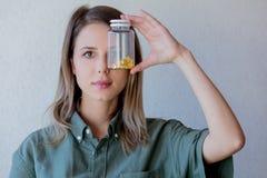 La donna tiene il barattolo trasparente con le pillole all'altezza d'occhio fotografia stock