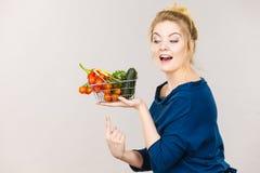La donna tiene il cestino della spesa con le verdure Fotografia Stock