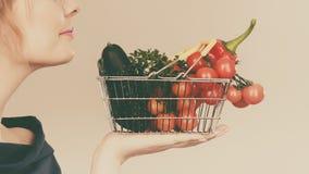 La donna tiene il cestino della spesa con le verdure, odoranti Immagine Stock