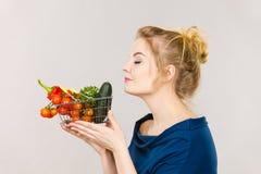 La donna tiene il cestino della spesa con le verdure, odoranti Fotografia Stock Libera da Diritti