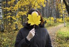 La donna tiene la foglia di acero gialla enorme nella mano, riguardante il suo fac Fotografie Stock Libere da Diritti
