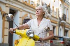 La donna tiene lo scooter& x27; volante di s fotografia stock