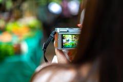 La donna tiene la macchina fotografica d'annata, prendente una foto del mercato di verdure locale fotografia stock libera da diritti
