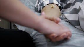 La donna tiene la mano che il suo amico con il catetere in ospedale la calma, primo piano delle mani archivi video
