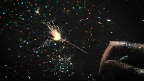 La donna tiene la stella filante del fuoco d'artificio sul contesto festivo video d archivio