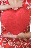 La donna tiene un cuore rosso di fronte al busto Immagini Stock