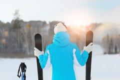 La donna tiene un paio di corsa con gli sci che cerca il pendio dello sci Fotografia Stock Libera da Diritti