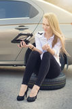 La donna tiene una presa Automobile rotta su un fondo La donna si siede su una ruota riparazione della donna un'automobile Sfondo Immagine Stock