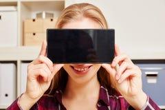 La donna tiene uno smartphone davanti alla sua testa Fotografia Stock