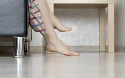 La donna tira le sue gambe dal letto fotografie stock