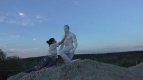 La donna tocca un uomo con una statua stock footage