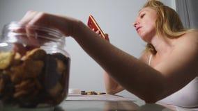 La donna triste affamata si siede in un salone ad una tavola alla notte, mangia un fegato ed utilizza il suo smartphone archivi video