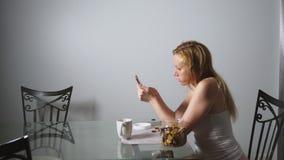 La donna triste affamata si siede in un salone ad una tavola alla notte, mangia un fegato ed utilizza il suo smartphone stock footage