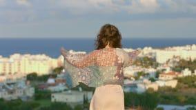 La donna triste avvolta in sciarpa esamina la città della spiaggia, il paesaggio stupefacente, ora magica video d archivio