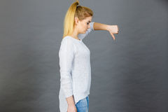 La donna triste che mostra il pollice giù gesture fotografia stock