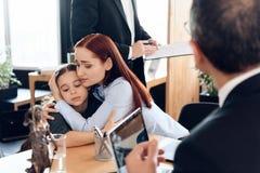 La donna triste dai capelli rossi abbraccia piccolo ragazza turbata che si siede nell'ufficio del ` s dell'avvocato per il divorz immagini stock