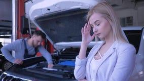 La donna triste del cliente si è rovesciata circa l'automobile rotta con il cappuccio aperto che è riparato dal meccanico in dist stock footage