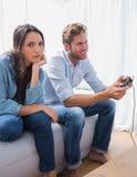 La donna triste si è infastidita che il suo partner sta giocando i video giochi Immagini Stock