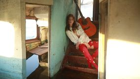 La donna triste si siede con la chitarra dentro di vecchia nave stock footage