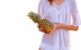 La donna in tunica bianca con l'ananas sulla spiaggia ha illuminato il sole Fotografie Stock