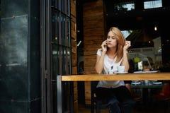 La donna turbata ha sentito le cattive notizie con il telefono cellulare mentre rilassandosi dopo il giorno del lavoro in caffett Fotografie Stock